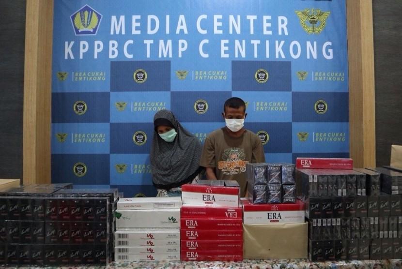 Tersangka bersama hasil sitaan barang penyelundupan berupa rokok ilegal.