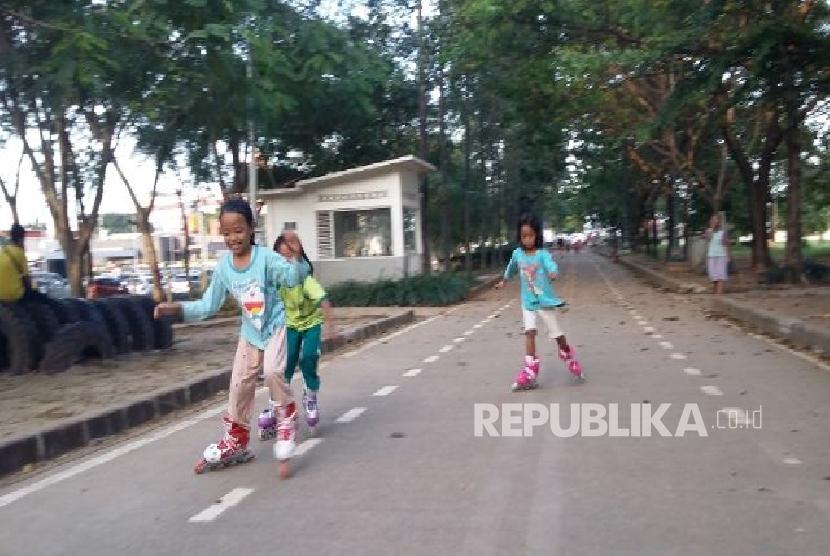 Tiga orang anak bermain sepatu roda di taman BKT Duren Sawit Jakarta, Selasa (25/4).