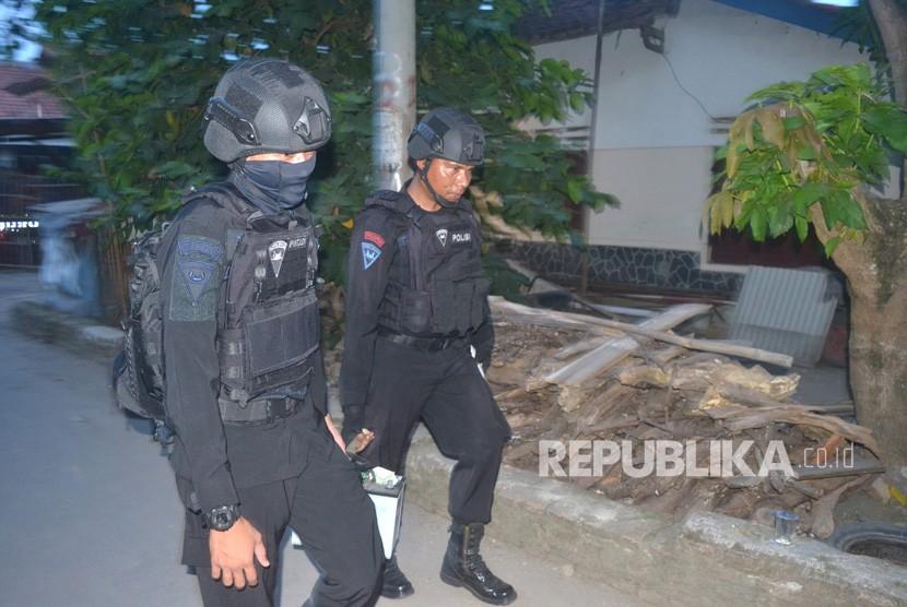 Tim Densus 88 membawa barang bukti saat penggeledahan usai penangkapan terduga teroris di Jemaras, Klangenan, Kab. Cirebon, Jawa Barat, Kamis (17/5). Operasi penangkapan juga digelar Densus 88 di Jombang.