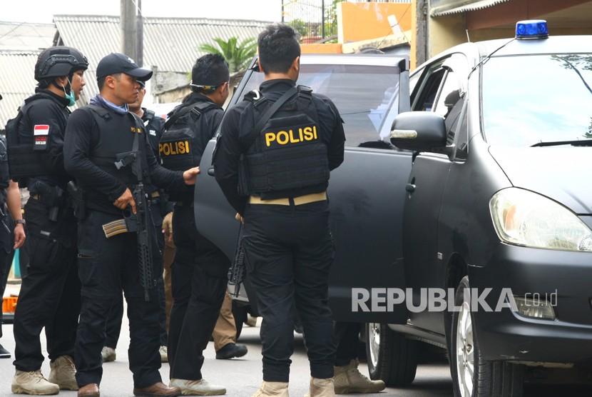 Tim Densus 88 mengamankan istri terduga Teroris saat dilakukan penggerebekan di Gempol, Tangerang, Banten, Rabu (16/5).