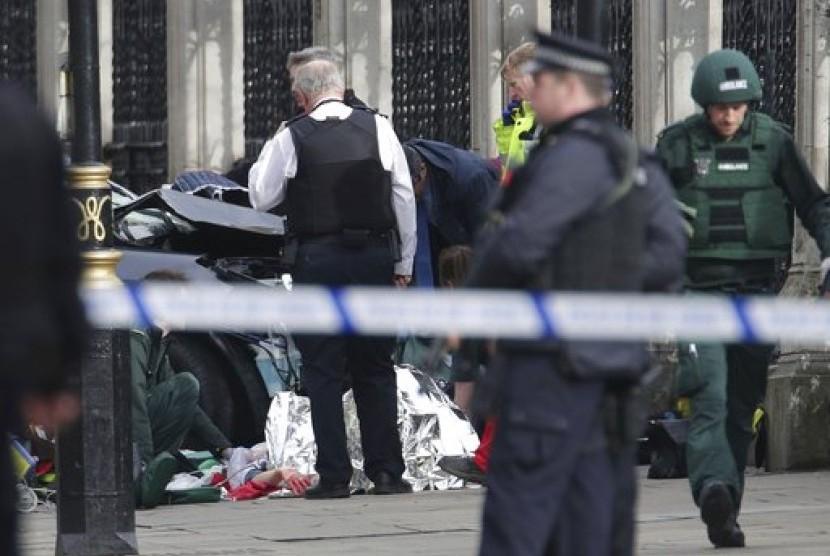 Tim penanganan darurat menangani seorang warga terkuka dekat Istana Westminster, London, Rabu (22/3). Serangan di luar gedung parlemen Inggris menewaskan lima orang.