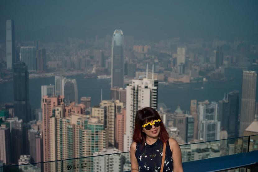 Turis berfoto dengan latar belakangan Kota Hong Kong.