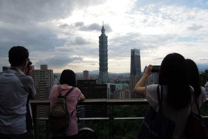 Turis sedang mengambil gambar bangunan paling ikonik Taiwan yakni Taipei 101.
