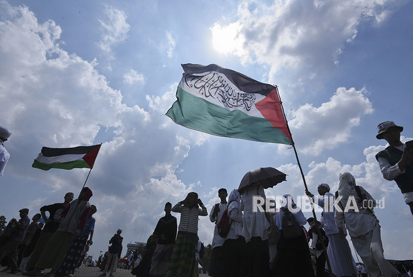 Participants of 115 rally raise Palestinian flags at National Monument (Monas) area, Central Jakarta, on Friday (May 11).