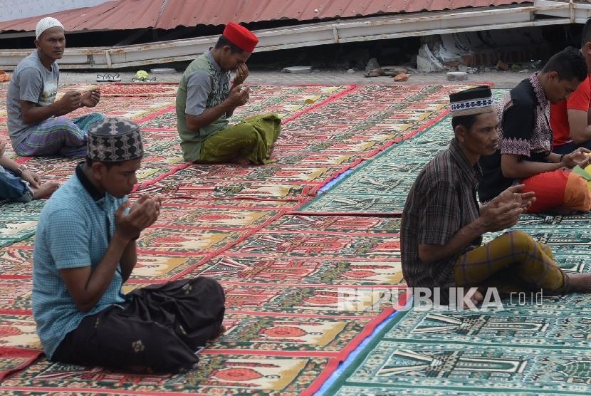 Umat muslim berdoa usai menunaikan Shalat Jumat di Masjid Jamik Quba, Pidie Jaya, NAD, Jumat (9/12).