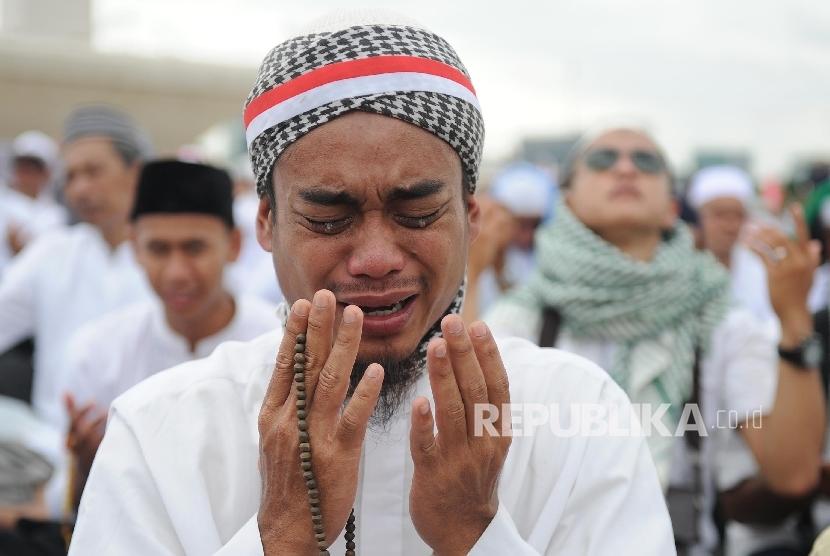 Umat muslim menangis saat berdoa di acara aksi damai di kawasan Monas, Jakarta, Jumat (2/12).