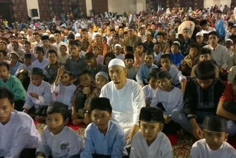Ustad Muhammad Arifin Ilham duduk bersama anak anak yatim piatu di mesjid Raya Sumatra Barat.