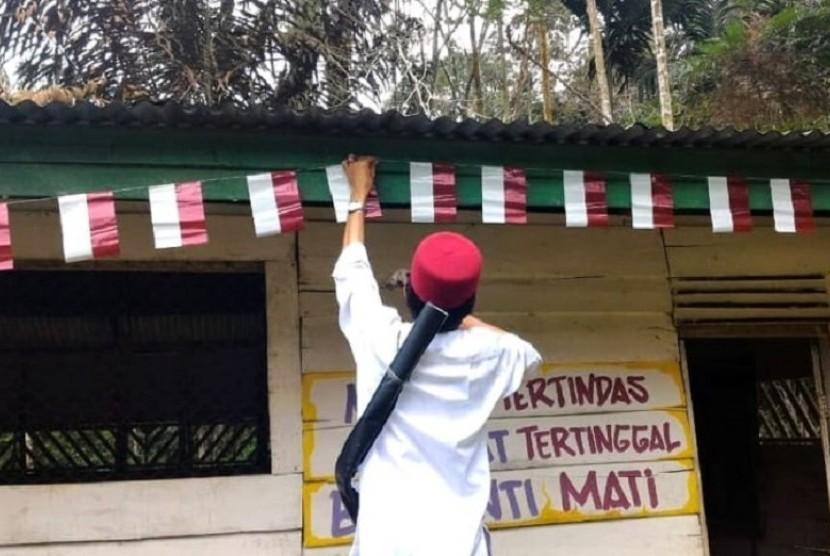 Ustaz Abdul Somad memasang bendera merah putih di rumah di permukiman Suku Talang Mamak, pedalaman Riau.