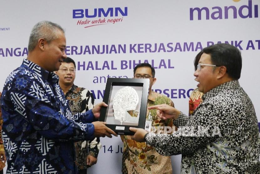 Wakil Direktur Utama Bank Mandiri Sulaiman A. Arianto (kanan) menyerahkan cindera mata kepada Direktur Utama PT. Pembangunan Perumahan (PP) Tumiyana (kiri) usai acara penandatanganan perjanjian kerjasama kedua belah pihak di Jakarta Jumat (14/7).