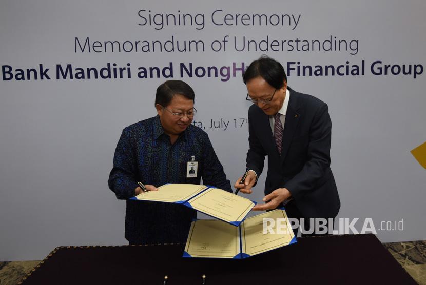 Wakil Direktur Utama Bank Mandiri Sulaiman A Arianto (kiri) dan Chairman & CEO NongHyup Financial Kim Yong Hwan bertukar lembar nota kesepahaman saat penandatangan kerjasama sejumlah bisnis perbankan di Plaza Mandiri, Jakarta (17/7).