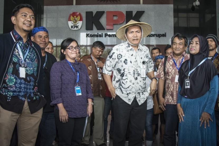 Wakil Ketua KPK Saut Situmorang (tengah) mengenakan caping yang diterima dari perwakilan Serikat Petani Pasundan di gedung KPK, Jakarta, Kamis (05/10). Sejumlah petani dari berbagai daerah yang tergabung dalam Komite Nasional Pembaruan Agraria (KNPA) memberikan dukungan kepada Komisi Pemberantasan Korupsi (KPK) untuk mengusut tuntas dan menindaklanjuti potensi korupsi yang sedang dan akan berlangsung di sektor agraria.