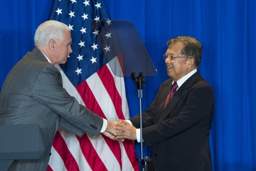 Wakil Presiden Jusuf Kalla (kanan) berjabat tangan dengan Wakil Presiden Amerika Serikat (AS) Michael R. Pence usai memberi sambutan dalam Business Leaders and Commercial Deal Signing, Jakarta, Jumat (21/4).