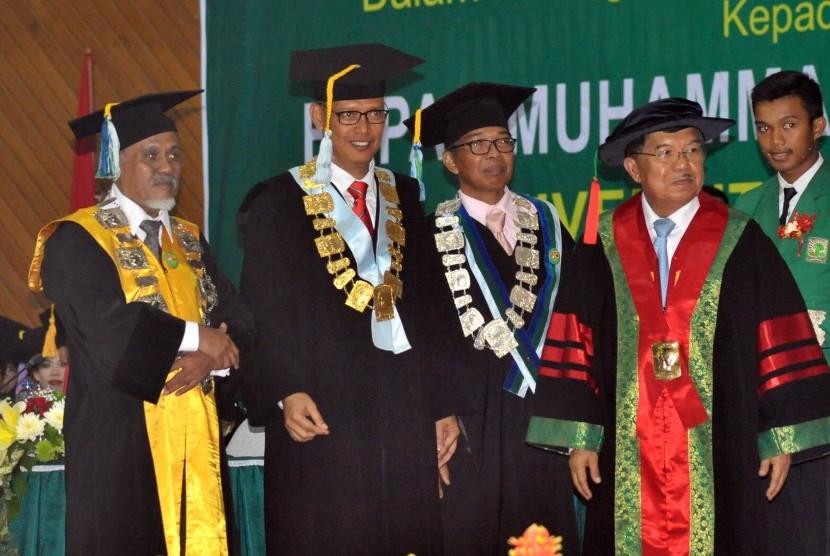 Wakil Presiden, Jusuf Kalla (kanan), didampingi Rektor Universitas Andalas (Unand), Tafdil Husni (dua kiri), Ketua Senat Akademik Unand, Ardinis Arbain (kiri) dan Ketua Majelis Guru Besar Unand, Darwin Amir (dua kanan), usai menerima gelar doktor kehormata