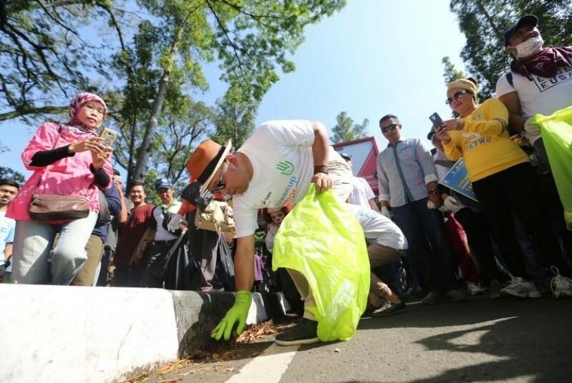 Wali Kota Bandung Ridwan Kamil memungut sampah  bersama ratusan warga di Car Free Day Dago, Ahad (8/10).