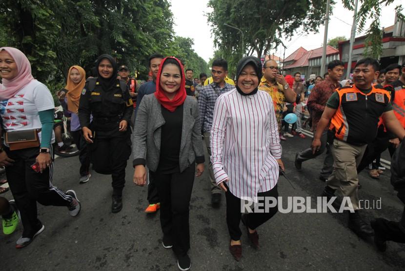 Wali Kota Surabaya Tri Rismaharini (kanan) bersama bakal calon Wakil Gubernur Jawa Timur Puti Guntur Soekarno (kiri) berjalan santai saat Hari Bebas Kendaraan Bermotor atau Car Free Day (CFD), di Darmo, Surabaya, Jawa Timur, Ahad (21/1).