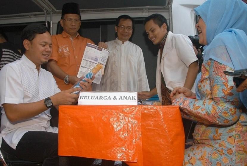 Walikota Bogor Bima Arya (kiri) bersama Wakil Walikota Bogor Usmar Hariman (kedua kiri) mendapat penjelasan tentang hasil analisa gizi saat peluncuran Mobil Curhat di Lapangan Sempur, Kota Bogor, Jabar, Minggu (6/7)