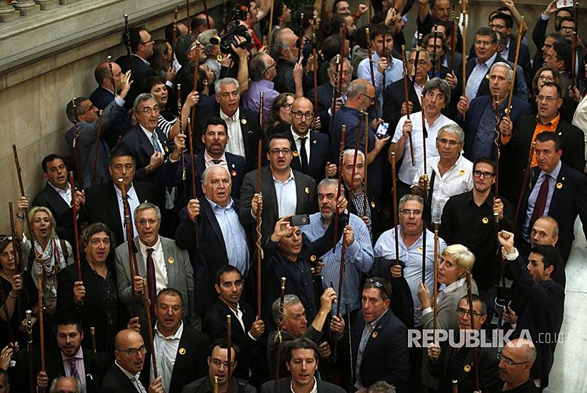 Walikota dari kota-kota di negara bagian Katalunya mengangkat tongkat di gedung parlemen lokal Katalunya setelah hasil voting memenangkan keputusan untuk memisahkan diri dari Spanyol