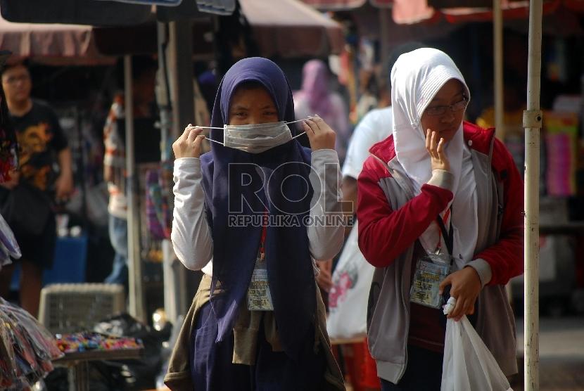 Wanita menggunakan masker untuk menghindari polusi udara.