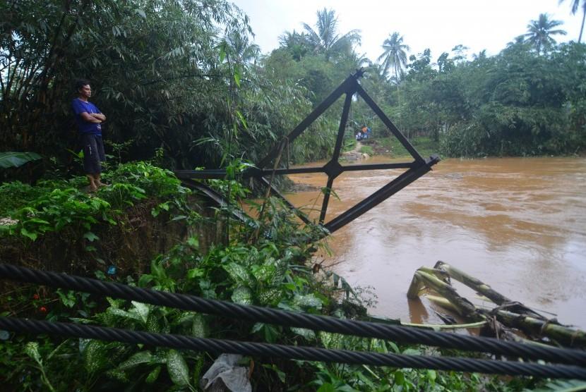 Warga berada di dekat sisa tiang jembatan gantung yang ambruk terbawa arus sungai Cibeurem, Desa Pajaten, Kabupaten Pangandaran, Jawa Barat, Sabtu (7/10). Hujan deras yang mengguyur wilayah Pangandaran mengakibatkan air sungai Cibeurem meluap serta mengikis jembatan yang menghubungkan antar dua desa sehingga aktivitas warga terganggu dan terpaksa harus menggunakan jalur yang berjarak lima kilometer.