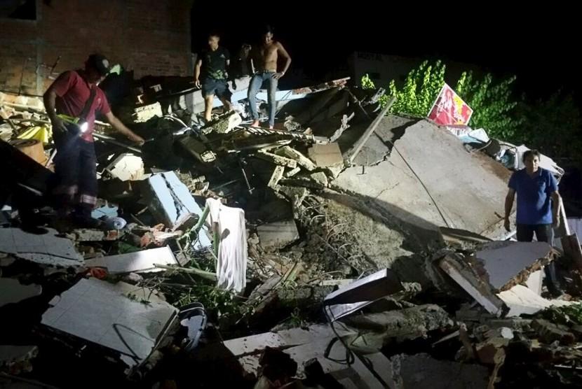 Warga berdiri atas runtuhan bangunan akibat gempa bumi berkekuatan 7,8 SR di Manta, Ekuador, Sabtu (16/4).