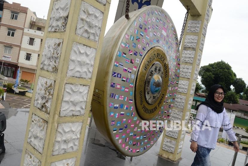 Warga berfoto di depan Gong Perdamaian Dunia (World Peace Gong) di Kota Ambon, Maluku, Rabu (8/2).