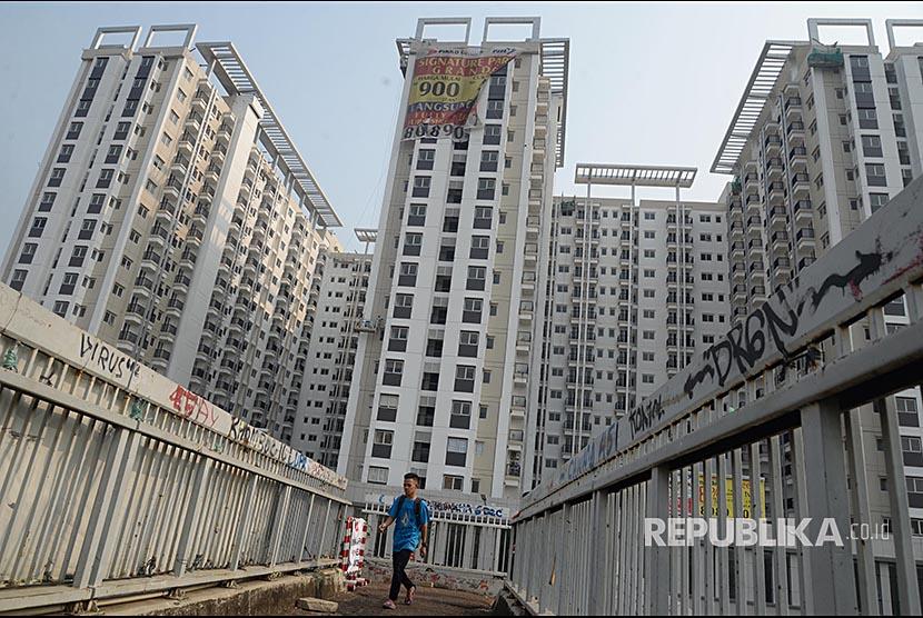 Warga berjalan di sebelah apartemen di kawasan Jakarta Timur.  Bank Indonesia (BI) menilai, sektor properti memiliki peran sangat penting dalam pembangunan perekonomian nasional (Ilustrasi)