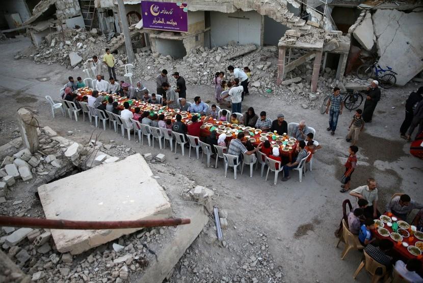 Warga berkumpul untuk berbuka puasa di antara reruntuhan gedung di kawasan Damaskus, Suriah yang dikuasai milisi.