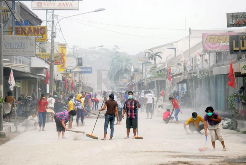 Warga bersama petugas TNI dan Kepolisian membersihkan abu vulkanik yang menyelimuti Jalan MT Haryono, Kutoarjo, Purworejo, Jawa Tengah, Sabtu (15/2). (Republika/Adhi Wicaksono)