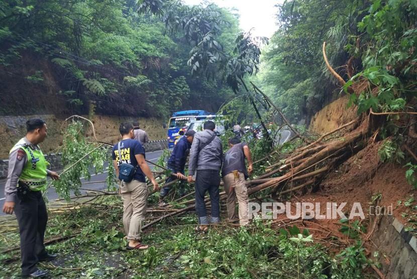 Warga bersama polisi bergotong royong mengevakuasi pohon tumbang yang menutupi ruas jalan Kiaradodot -Cikembulan di Desa Kadungora, Kabupaten Garut.
