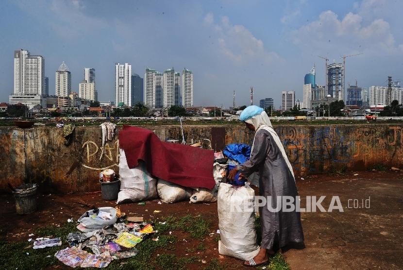 Warga brerjalan saat mengumpulkan sisa produk plastik di Jakarta, Senin (18/7)