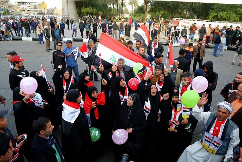 Warga Irak merayakan kemenangan militer yang berhasil mengalahkan ISIS di Tahrir Square, Baghdad, Irak, Ahad (10/12).