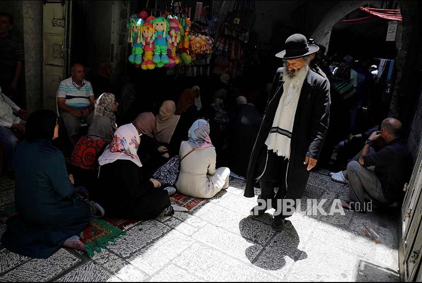 Warga Israel Ortodok melintasi warga Palestina di Kota Tua Yerusalem, Jumat (21/7)