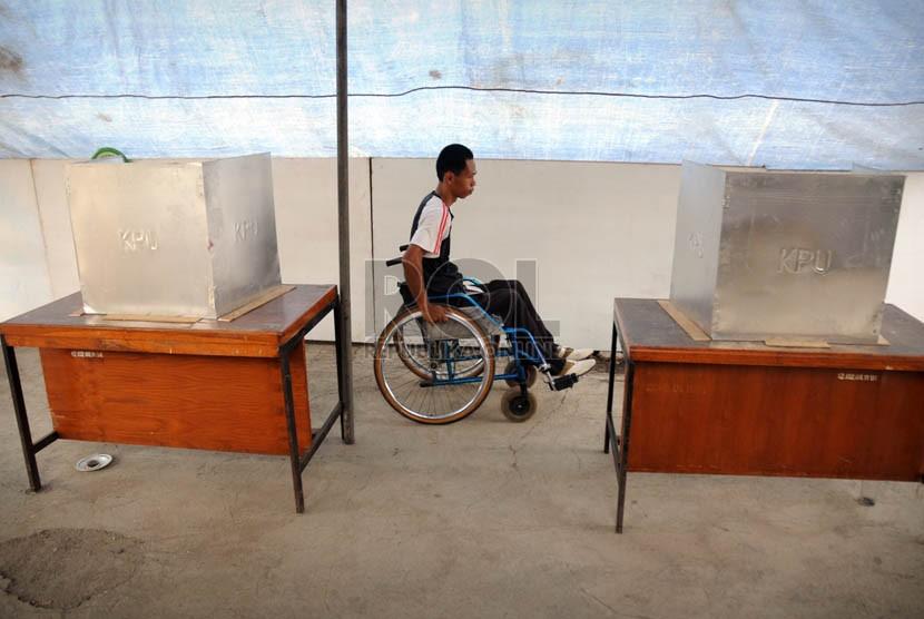 Warga Jakarta penyandang disabilitas tuna daksa dengan bantuan petugas, mengantre untuk menggunakan hak suaranya.  (Aditya Pradana Putra/Republika)
