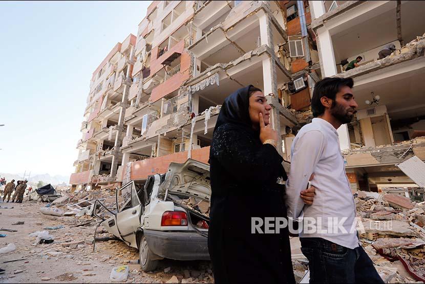 Warga Kota Sare Pole-Zahab propinsi Kermanshah melintasi reruntuhan bangunan yang rusak akibat gempa. Selasa (14/11).