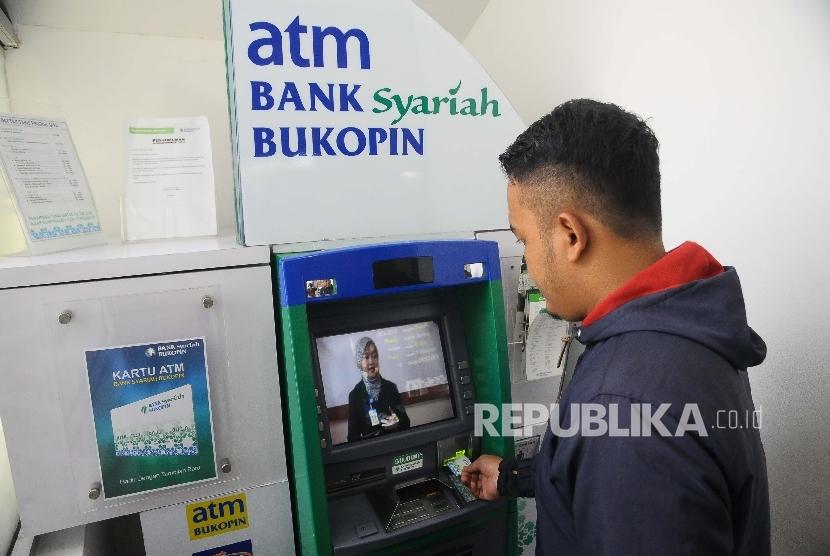 Warga melakukan transaksi menggunakan mesin ATM di Bank Syariah Bukopin, Jakarta, Ahad (5/3).