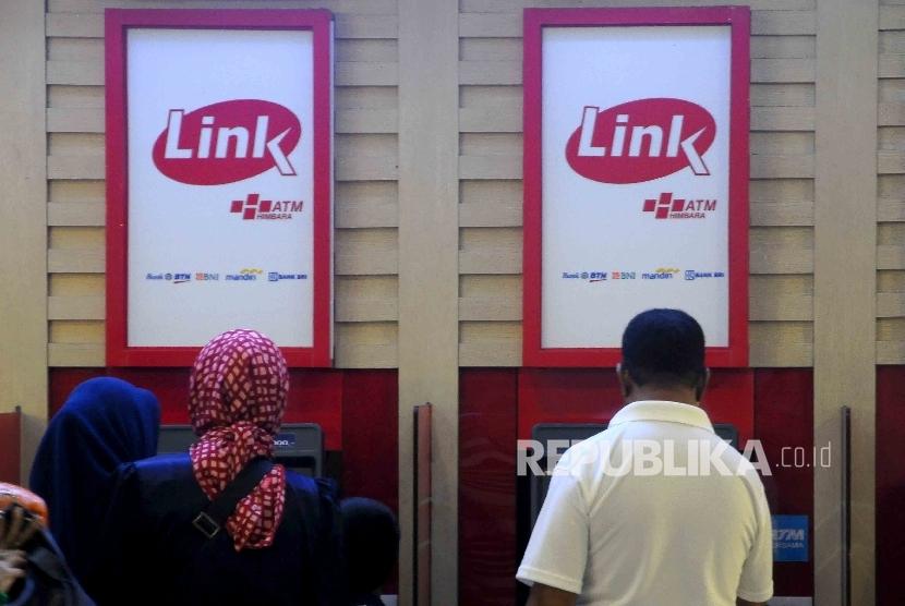 Warga melakukan transkasi menggunakan mesin ATM Himpunan Bank-Bank Milik Ngara (Himbara) di Pasar Tanah Abang, Jakarta, Ahad (9/10).