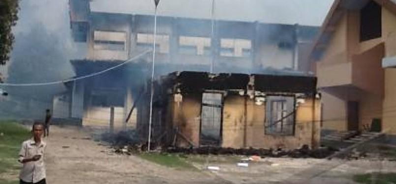 Warga melintas di samping bangunan KPUD Bima yang dibakar massa saat terjadi aksi ribuan pengunjuk-rasa menduduki kantor Bupati Bima, Kabupaten Bima, NTB, Kamis (26/1).