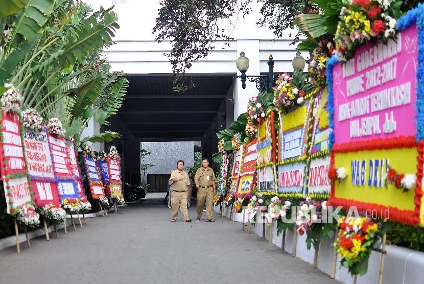 Warga melintas diantara karang bunga yang berisi ucapan terima kasih kepada Basuki Tjahaya Purnama dan Djarot Saiful Hidayat di Balai Kota DKI Jakarta, Senin (9/10).