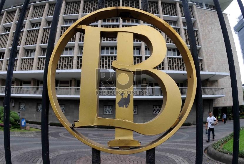 Warga melintas didekat logo Bank Indonesia, Jakarta Pusat, Rabu (1/7).