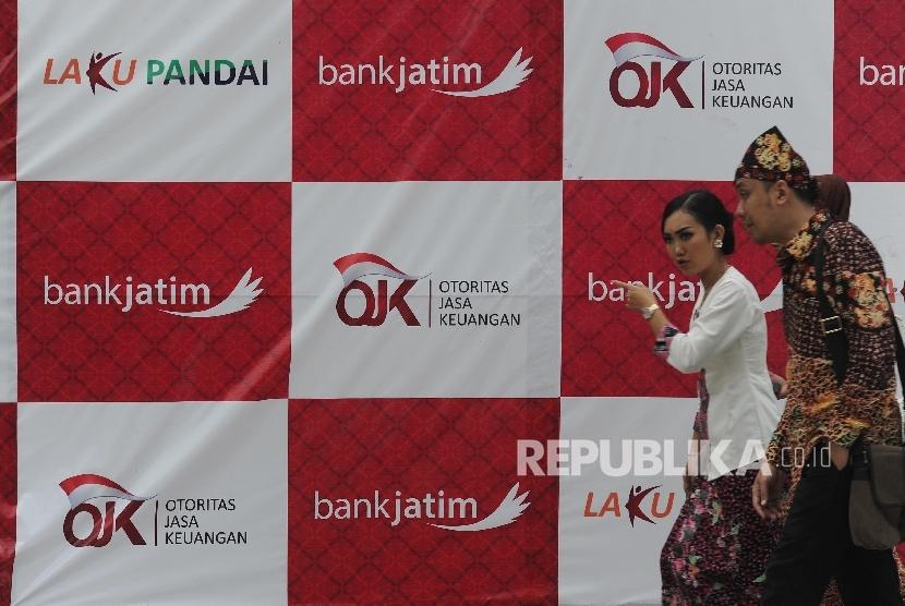 Warga melintas didepan tulisan Otoritas Jasa Keungan (OJK) saat peluncuran laku pandai Bank Jatim di Banyuwangi, Kamis (24/11).
