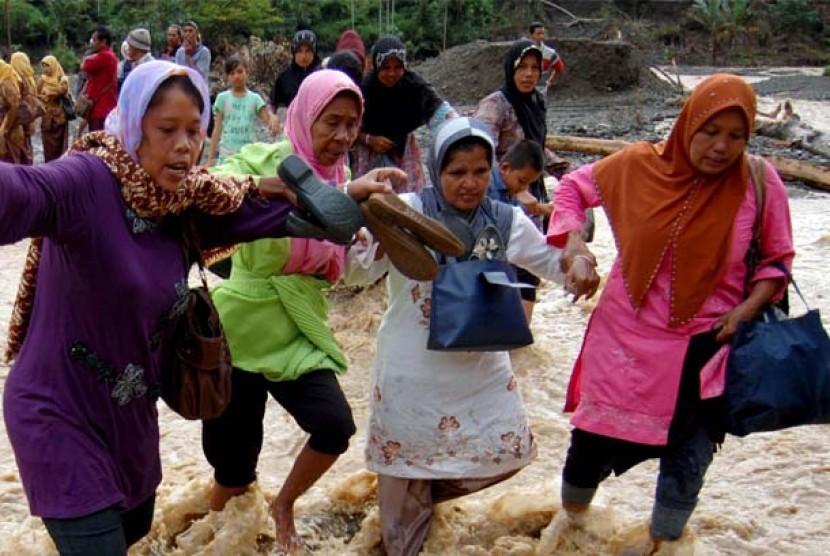 Warga melintasi banjir di Desa Lubuk Nilam, Kecamatan Tanse, Kabupaten Pidie, Provinsi Aceh, Kamis (1/3). Hingga hari keempat banjir bandang Tangse bertambah parah, tiga titik jalur darat kembali terputus, warga di lima desa meliputi Lubuk Nilam, Blang Mal