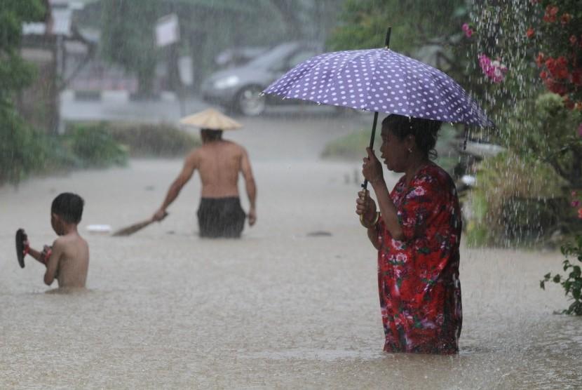 Warga melintasi banjir yang merendam wilayah permukimannya. (ilustrasi)