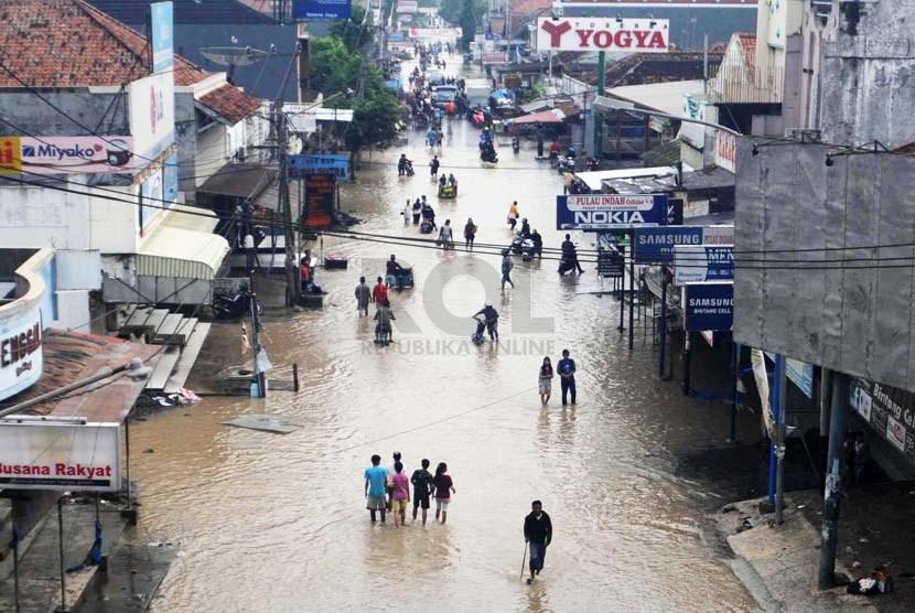 Warga melintasi jalan yang terkena banjir di kawasan Pantura, Pamanukan, Subang, Jabar, Rabu (22/1).