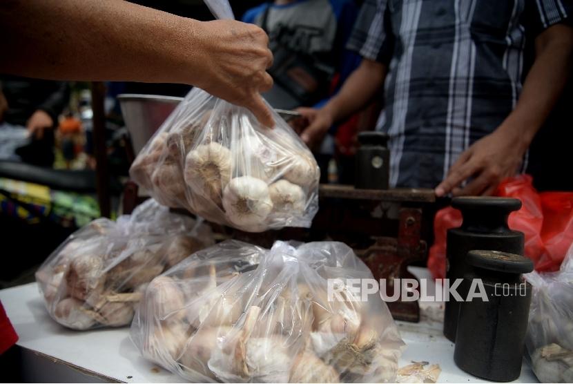 Warga membeli bawang putih saat dilaksanakananya operasi pasar komoditas bawang putih di Pasar Senen, Jakarta, Kamis (1/6).