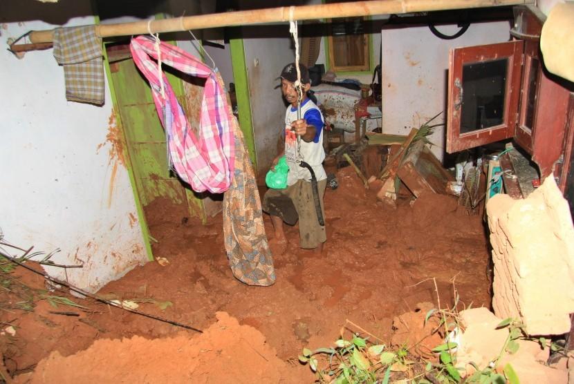 Warga membersihkan meterial tanah longsor yang menghantam rumahnya di Desa Kalijati, Kabupaten Pangandaran, Jawa Barat, Sabtu (7/10). Akibat hujan deras yang mengguyur Kabupaten Pangandaran mengakibatkan empat orang tewas tertimbun tanah longsor.