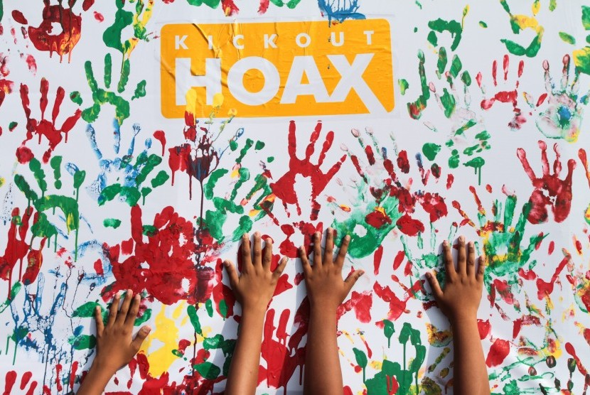 Warga membubuhkan cap tangan saat aksi Kick Out Hoax di Solo, Jawa Tengah, Minggu (8/1).
