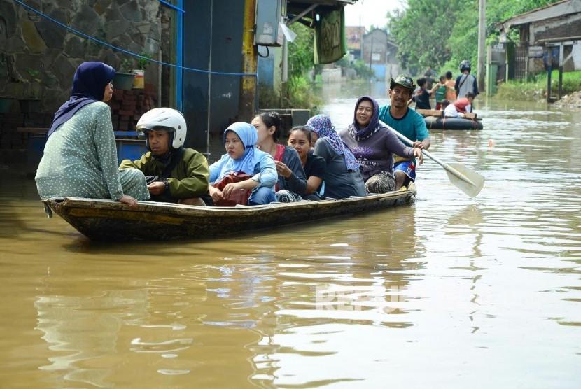 Warga menaiki perahu, di jalan yang sudah terendam banjir. ilustrasi