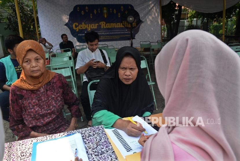 Warga mendapatkan layanan kesehatan gratis bersama Lazismu di halaman Masjid Al-Huda Pimpinan Cabang Muhammadiyah Tebet, Jakarta Selatan, Ahad (18/6).