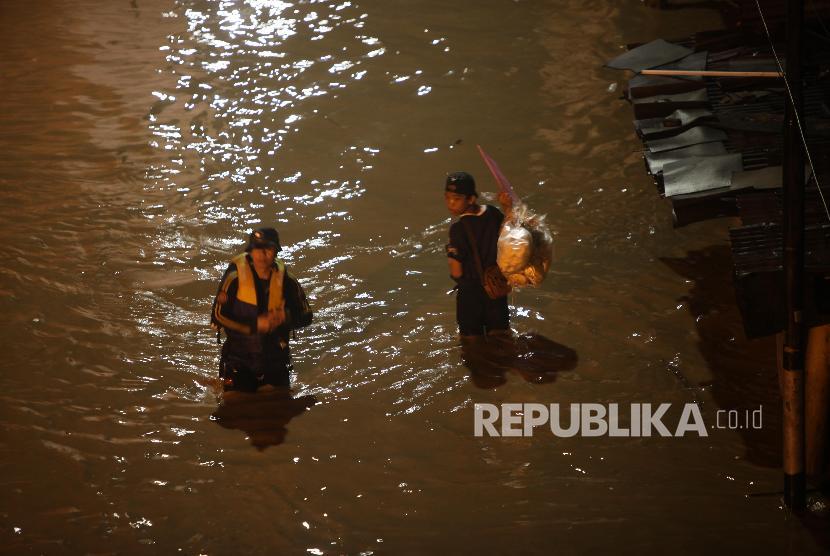Warga menerobos banjir di kawasan Cililitan, Jakarta, Senin (5/2) malam. Banjir yang merendam kawasan tersebut akibat luapan Kali Ciliwung yang merupakan kiriman dari Bendung Katulampa, Bogor.
