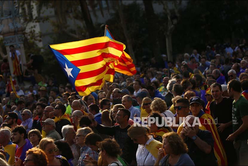 Warga mengibarkan bendera Katalan pada unjuk rasa di Barcelona
